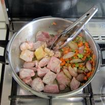 Shove the vegetables aside and brown the very lightly dredged meat cubes.