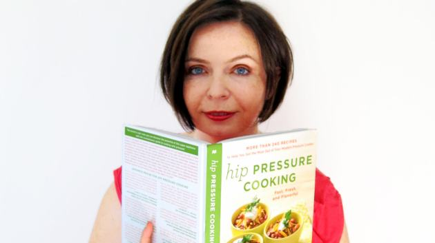 "The author, Laura Pazzaglia, peeks from behind a copy of her new coobook ""Hip Pressure Cooking: Fast, Fresh and Flavorful""."