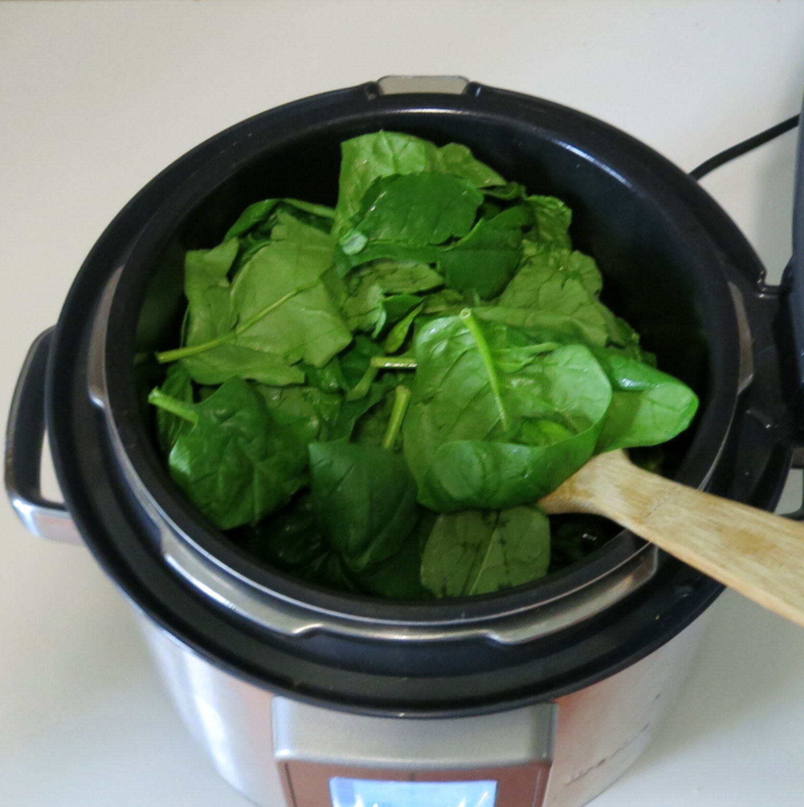Add spinach leaves to pressure cooker base.