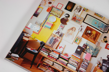 wall covered in art with a coffee table stacked with art and interior design books