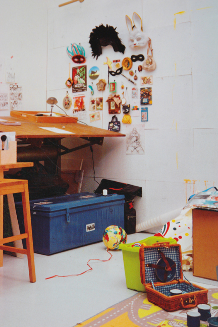 workspace with one wall decorated with various masks