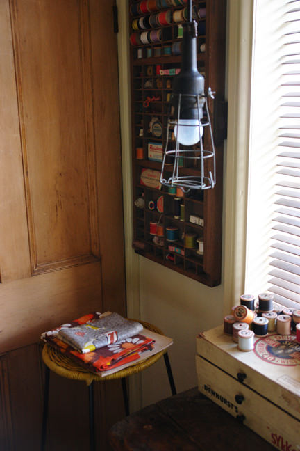 view of our craft & sewing room showing a vintage printers tray full of cotton reels