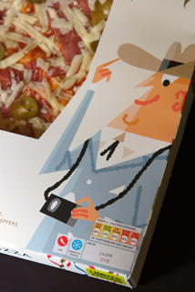 detail from a Marks and Spencer New York pepperoni pizza box showing a cartoon illustration of a Texan tourist wearing a stetson and a camera around his neck