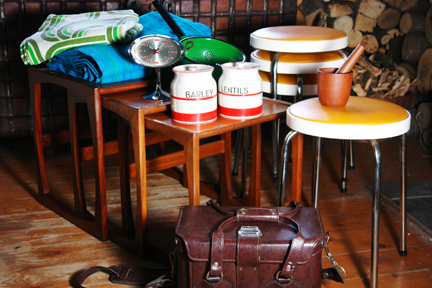 selection of recently acquired vintage items including a G Plan nest of teak tables, orange seated Chair Centre stacking stools, green & blue striped curtains, Rhythm pedestal clock, Scandinavian teak mortar & pestle, Hinomoto vinyl camera bag and red & white Kleen Kitchen Ware jars