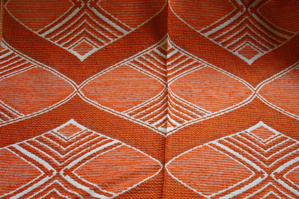 detail of pattern from a bolt of vintage orange Draylon fabric