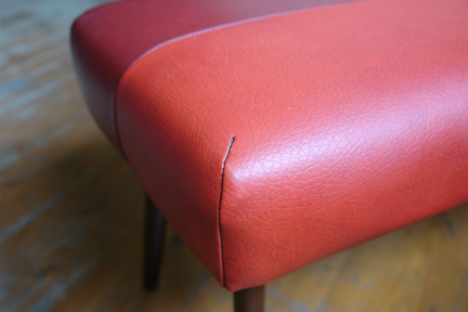 detail from a vintage 1950s footstool with red vinyl seat