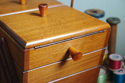detail of vintage wooden sewing box with reels of thread
