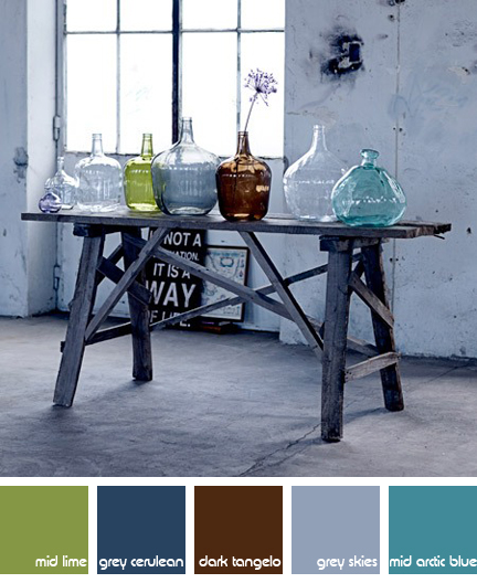 collection of vintage coloured bottles on an industrial trestle table