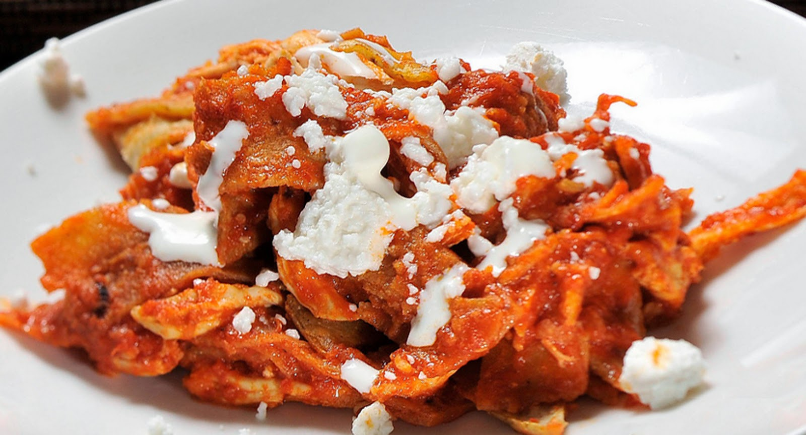 chilaquiles mexican cuisine Chilaquiles $1550 deep-fried tortilla chips, homemade sauce, topped with sour cream, onions, and crumbled cheese, served with black beans.