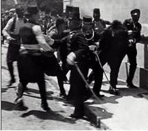 El 28 de junio de 1914, tuvo lugar en Sarajevo (la actual capital de Bosnia-Herzegovina) el asesinato del archiduque de Austria Francisco Fernando de Habsburgo y de su esposa. El atentado mortal contra el heredero de la corona austro-húngara, a manos de un nacionalista serbio, terminó por desencadenar la I Guerra Mundial, aunque no fue sino la acción de un fanático. La imagen muestra el instante en que resultó detenido el autor del asesinato, el joven serbio Gavrilo Princip.