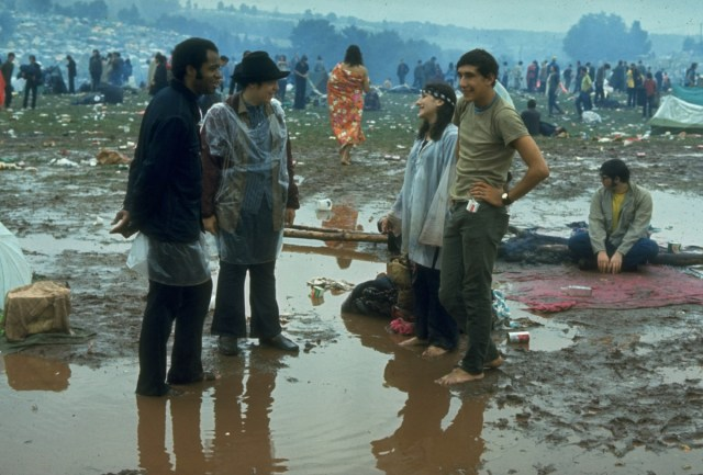 Woodstock attendees standing in muddy puddles after a rainstorm swept through.