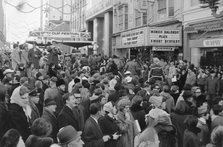 Crowds occupy Sparks Street for the 1967 Grey Cup Festival. This time, the Centre Theatre catered to the out-of-town crowds with Mondo Balordo and Sweet Ecstacy. The completed Toronto Dominion branch and Montreal Trust building are visible in the background. Image: Ted Grant / LAC