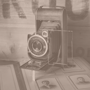 antique camera sitting on old photographs