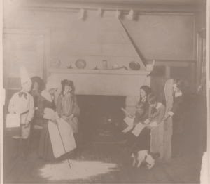 historical photo family sitting by fireplace