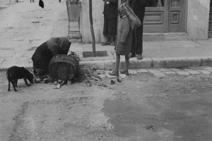 image of a woman, child and stray dog searching for food in the garbage in piraeus, greece at the crossroads of george the first and praxitelous streets, winter 1941-1942. this image has been reproduced with kind permission of the international committee of the red cross