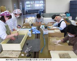 Volunteers cleaning documents damaged by prolonged submersion in tsunami seawater.