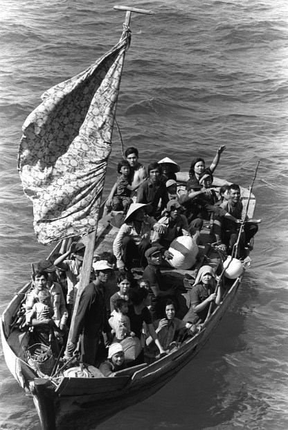 35 Vietnamese refugees wait to be taken aboard the amphibious command ship USS BLUE RIDGE (LCC-19). They are being rescued from a 35 foot fishing boat 350 miles northeast of Cam Ranh Bay, Vietnam, after spending eight days at sea. Photo by Phil Eggman