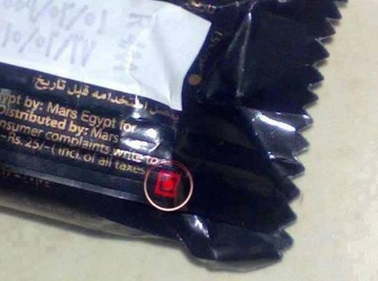 Picture Suggesting Be Aware of Red Dot inside a Red Square Symbol Shown on Chocolate Bars
