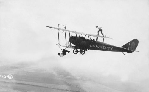 Image about Wing walkers show off above and below a biplane. c. 1920