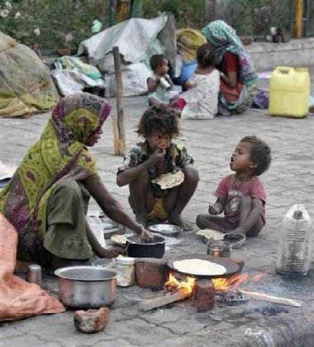 Image of Homeless children eating food on a footpath of Ahmedabad