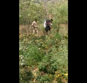 Image of Police carrying farmer Kotaiah through fields