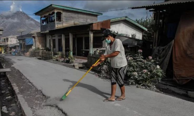 Image of Locals sweep up ash following volcanic eruption