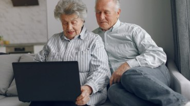 Old couple searching on the laptop