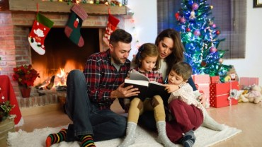 Family reading book near the Christmas tree