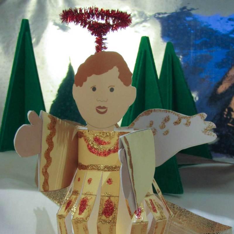 Dieser Engel hat rötliches Haar und trägt ein hell-gelbes Engelskleid. Sein Heiligenschein besteht aus einem glitzenden Pfeiffenreiniger. Es ist ein kleines Lampion.