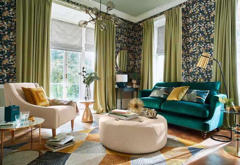 Salón decorado en tonos verdes con papel pintado con motivos vegetales y detalles en dorado