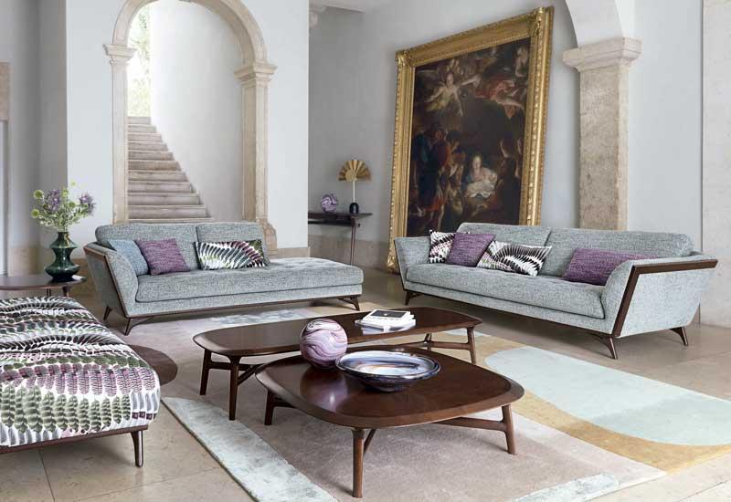 Salón con sofás grises y cojines morados y un cuadro XL con marco dorado apoyado en el suelo
