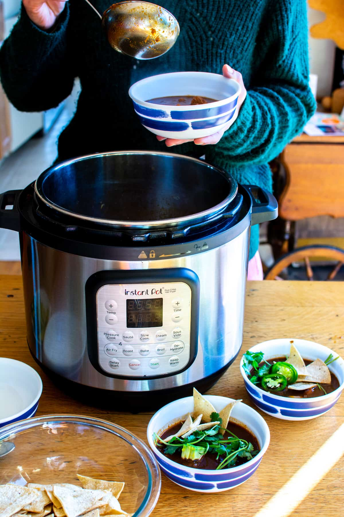 A woman in a green sweater ladling soup into a small bowl out of an Instant Pot sitting on a wood table.