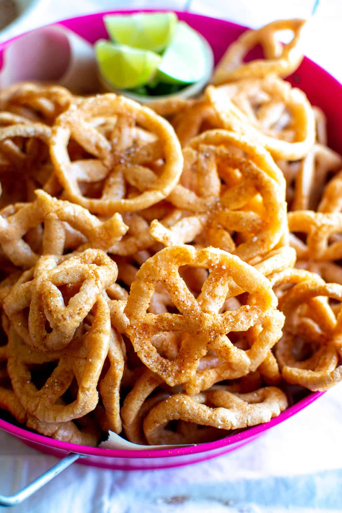 Mexican chips in wheel shapes sprinkled with homemade Chile spice mix in a pink tray.