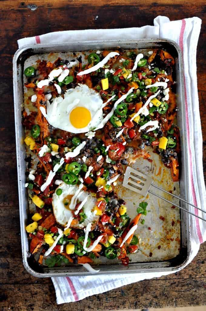 A sheet pan of Sweet Potato Breakfast Nachos on a wooden table with a white towel and spatula.