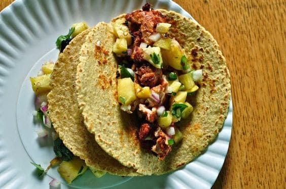 Tacos al Pastor, the classic taco truck staple can easily be made at home with this step-by-step recipe. Top with a grilled pineapple salsa for a sweet and spicy pork taco.