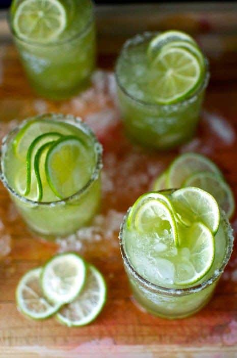 Four glasses sitting on a cutting board filled with ice, green liquid, and lime wheels.