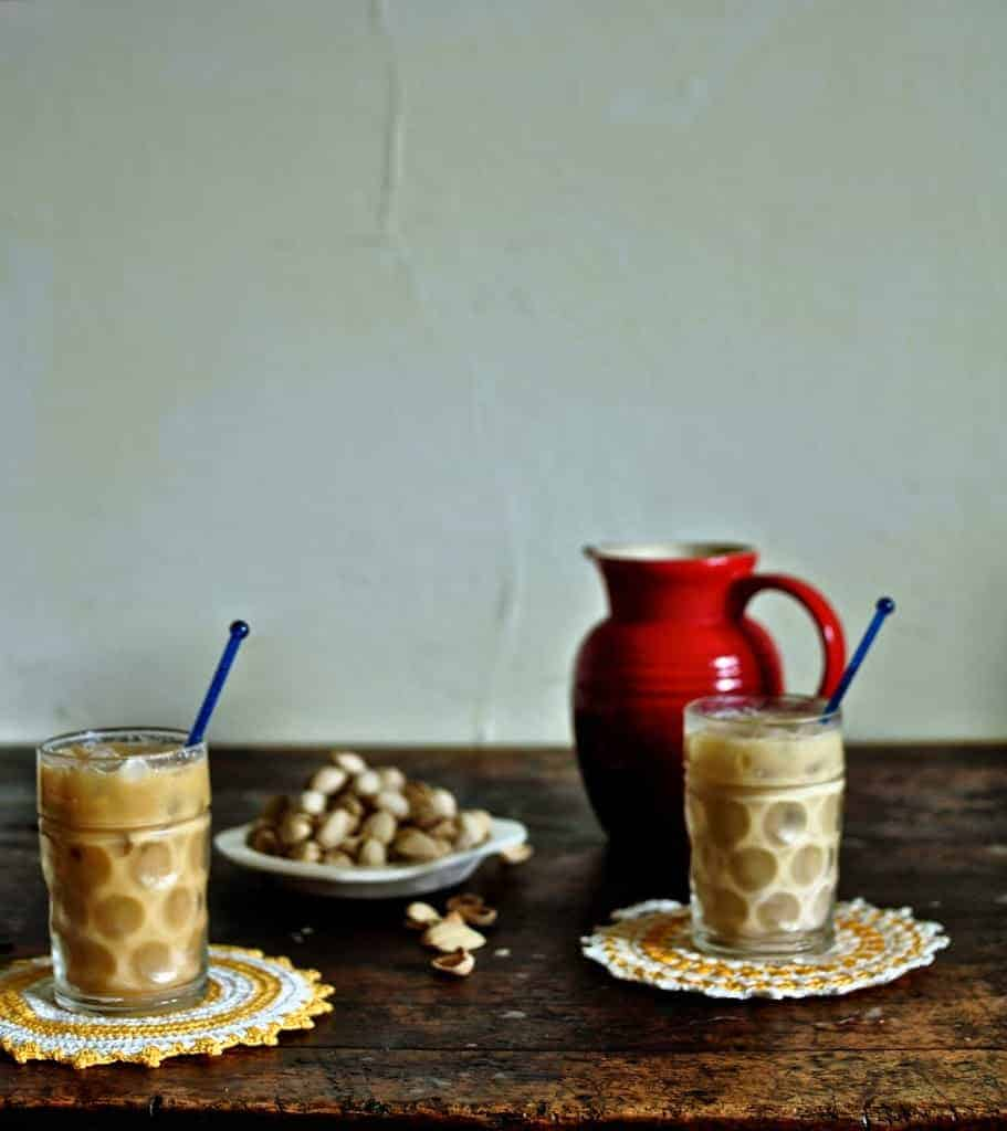 Two glasses of ice coffee sitting on a wooden table with a plate of pistachios behind them.