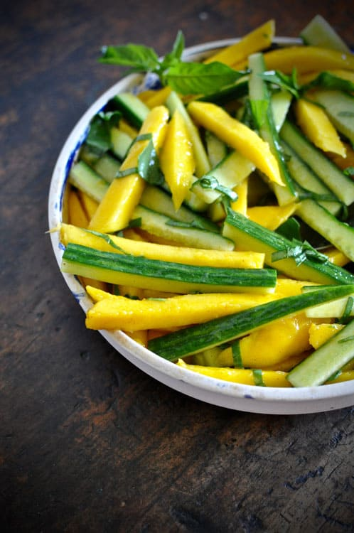 A shallow bowl with Mango-Cucumber Salad and fresh basil leaves sitting on a wooden table.