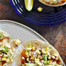 Several fish tacos with sweet corn salsa on a white platter and then another one on a blue plate with a lime wedge.