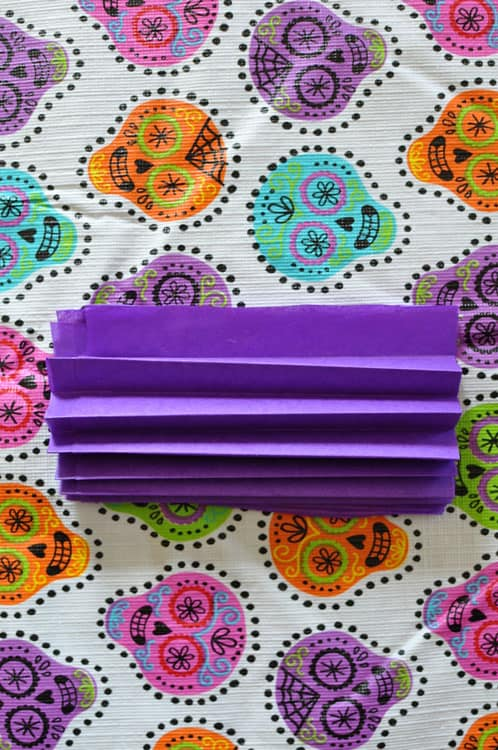 Purple tissue paper folded on a Day of the Dead tablecloth decorated with Calaveras.