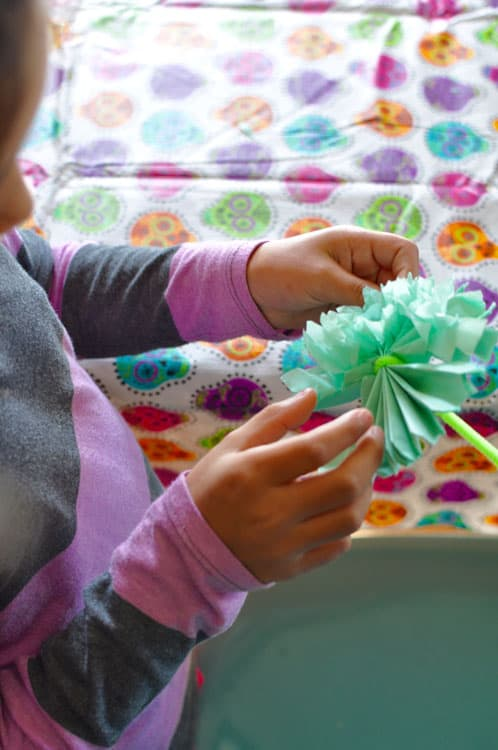 A girl's hand unfolding a aqua piece of tissue paper with a green pipe cleaner.