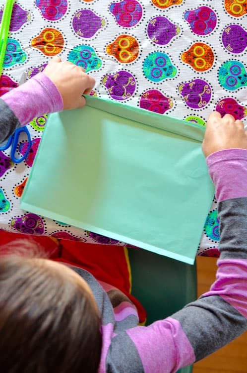 Girl sitting at a table folding light blue tissue paper on a Calavera tablecloth.