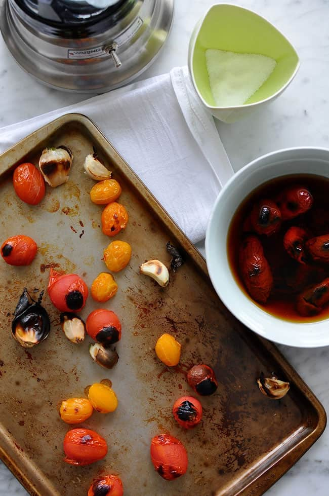 Garlic and cherry tomatoes that have been charred sitting on a baking sheet next to dried chiles soaking in water.