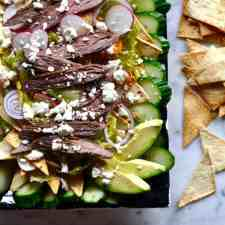This recipe combines Salpicon salad and Fattoush salad with seasoned steak, oven-baked flatbread crisps, avocado, feta cheese, and spicy chipotle dressing.