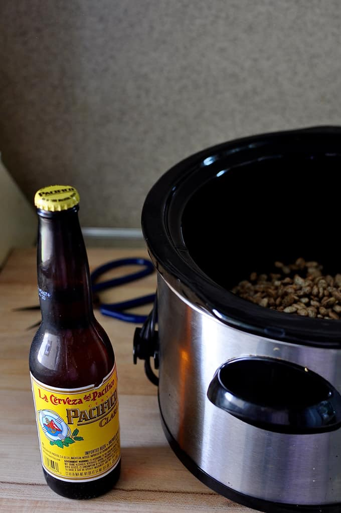 Bottle of beer next to a slow cooker on a wooden cutting board.