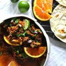 An overhead image of shredded pork with orange wedges in a white bowl sitting on a white tablecloth.