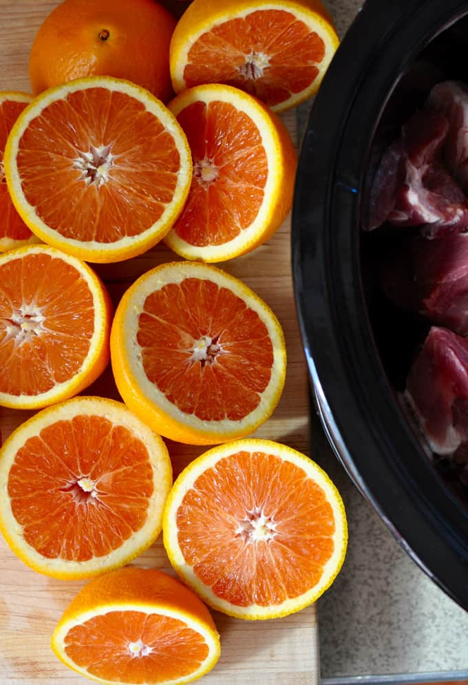A pile of oranges cut in half sitting on a wooden cutting board next to a black slow cooker pot with pork in it.