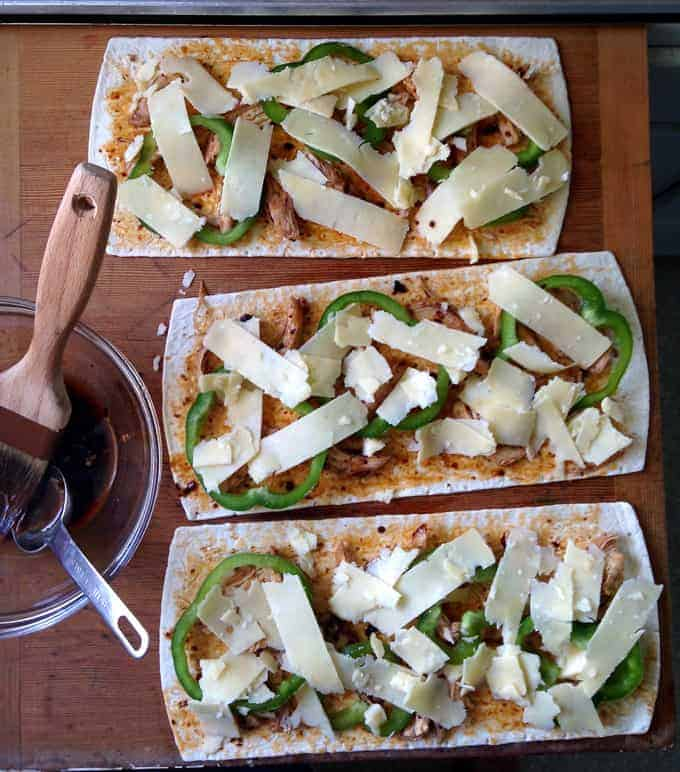 Flatbread pizzas getting ready to go on the grill sitting on a wooden board.