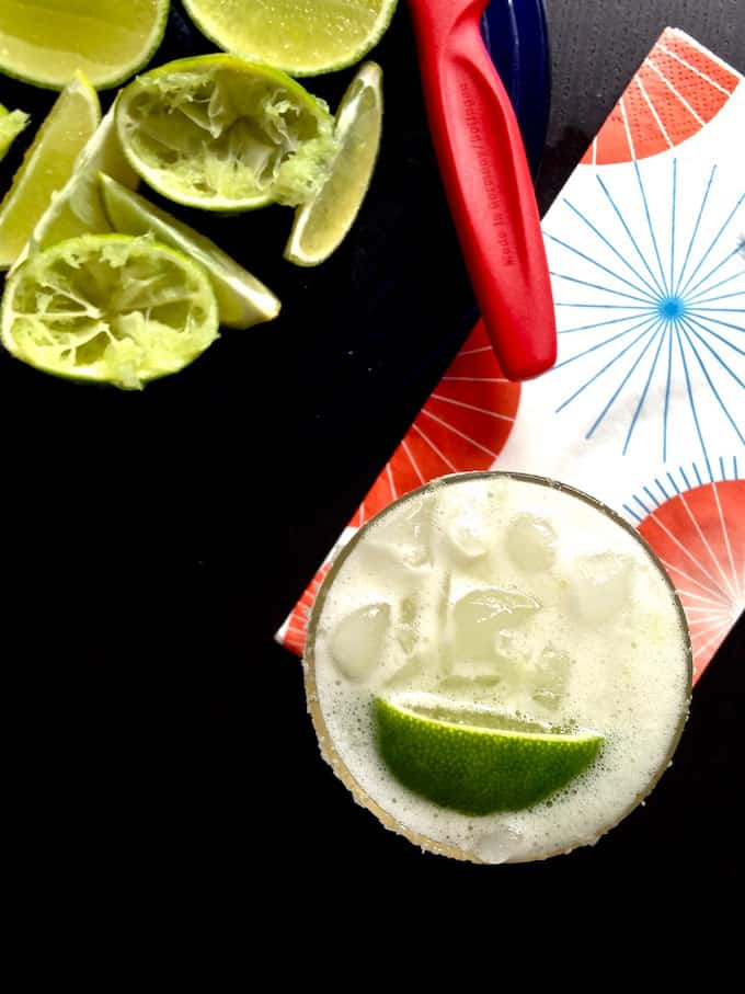Glass with ice and a margarita in it and a lime wedge floating on top.