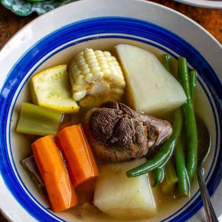 A blue and white bowl filled with Caldo de Res a Mexican beef and vegetable soup with carrots, green beans, beef, and corn.